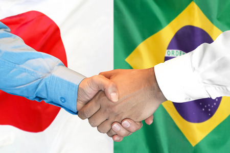 Business handshake on the background of two flags. Men handshake on the background of the Brazil and Japan flag. Support concept Zdjęcie Seryjne