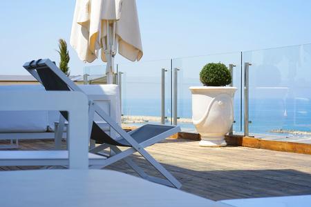 Interior of a large hotel balcony, villas. Beautiful balcony with white divans. White interior concept of a large balcony balcony. White color view of the morning horizon of the sea, the ocean.