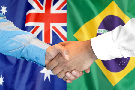 Business handshake on the background of two flags. Men handshake on the background of the Brazil and Australia flag. Support concept