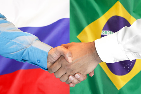 Business handshake on the background of two flags. Men handshake on the background of the Brazil and Russia flag. Support concept