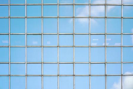 Finestre di vetro blu del grattacielo della costruzione di affari della città moderna della facciata. Condomini moderni nel nuovo quartiere. Finestre di un edificio, trama.