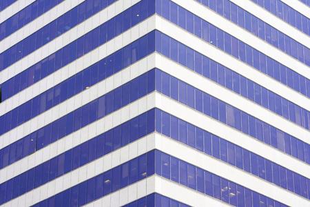 Angle modern business building skyscraper blue glass windows. Windows of facade. Modern apartment buildings in new neighborhood. Windows of a building, texture.