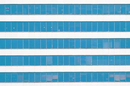 Glass blue Windows of facade modern city business building skyscraper. Modern apartment buildings in new neighborhood. Windows of a building, texture.