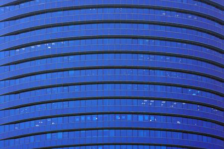 Glass blue square Windows of facade modern city business building skyscraper. Modern apartment buildings in new neighborhood. Windows of a building, texture.
