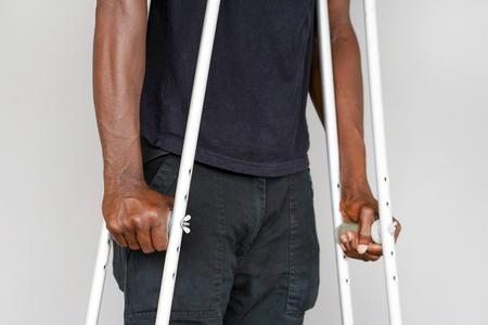 African man on crutches on a gray background. Close-up man walking with crutches.