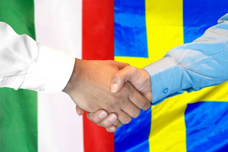 Business handshake on the background of two flags. Men handshake on the background of the Italy and Sweden flag. Support concept