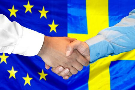 Business handshake on the background of two flags. Men handshake on the background of the European Union and Sweden flag. Support concept