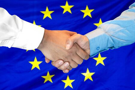 Business handshake on European Union flag background. Men shaking hands and European Union flag on background. Support concept 写真素材