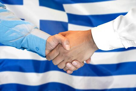 Business handshake on Greece flag background. Men shaking hands and Greece flag on background. Support concept 写真素材