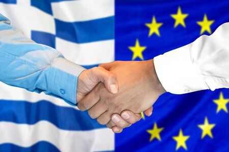 Business handshake on the background of two flags. Men handshake on the background of the Greece and European Union flag. Support concept