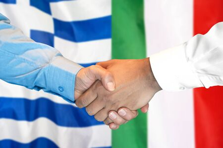 Business handshake on the background of two flags. Men handshake on the background of the Greece and Italy flag. Support concept