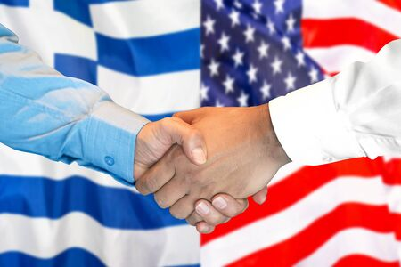 Business handshake on the background of two flags. Men handshake on the background of the Greece and United States of America flag. Support concept