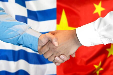 Business handshake on the background of two flags. Men handshake on the background of the Greece and China flag. Support concept