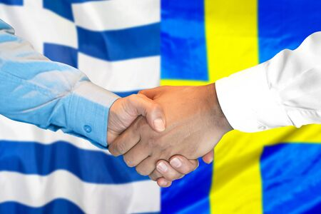 Business handshake on the background of two flags. Men handshake on the background of the Greece and Sweden flag. Support concept Stock Photo
