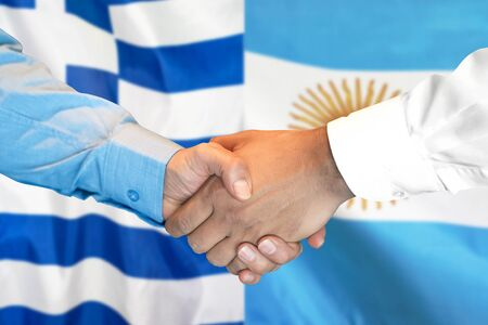 Business handshake on the background of two flags. Men handshake on the background of the Greece and Argentina flag. Support concept Stock Photo
