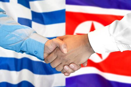 Business handshake on the background of two flags. Men handshake on the background of the Greece and North Korea flag. Support concept