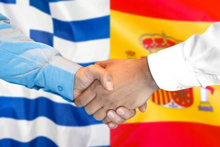 Business handshake on the background of two flags. Men handshake on the background of the Greece and Spain flag. Support concept
