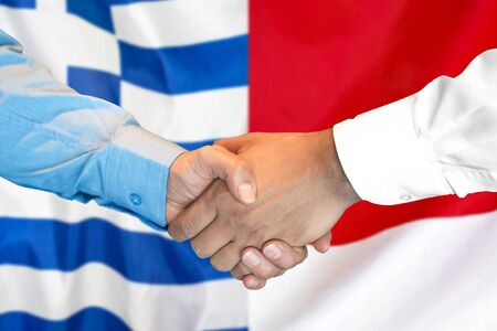 Business handshake on the background of two flags. Men handshake on the background of the Greece and Monaco flag. Support concept