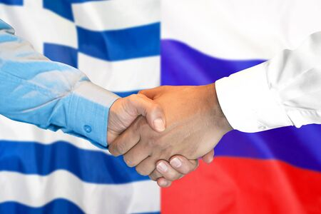 Business handshake on the background of two flags. Men handshake on the background of the Greece and Russia flag. Support concept
