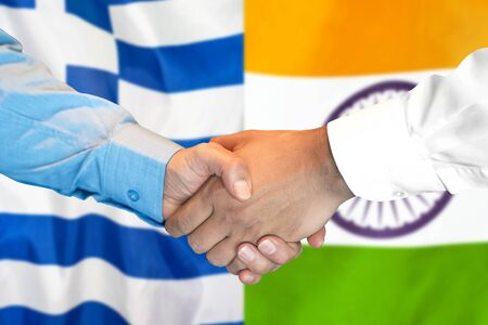 Business handshake on the background of two flags. Men handshake on the background of the Greece and India flag. Support concept Stock Photo