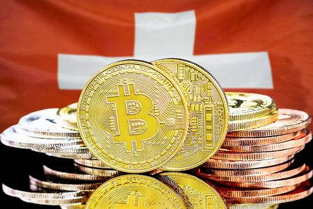 Concept for investors in cryptocurrency and Blockchain technology in the Switzerland. Bitcoins on the background of the flag Switzerland. Stock Photo