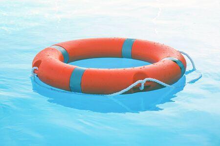 Orange lifebuoy pool ring float on blue water. Life ring floating on top of sunny blue water. Life ring in swimming pool Stock Photo