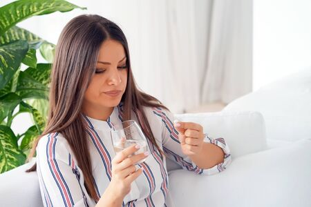 Portrait of Woman holding pill glass of water at home on the sofa. Depressed unhealthy woman, about to take antidepressant pill, emergency contraceptive, painkiller for painful periods.