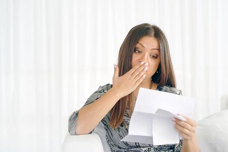 Office worker woman reading negative news in letter. Shocked beauty girl business manager received layoff message letter from company feeling surprised. Banco de Imagens