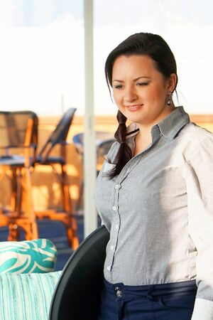 The waitress takes the customers order in the hotel restaurant. Morning time. The girl is smiling. A waiter woman takes an order holding the tray by hand. The concept of service.