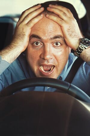 Human emotion face expression. Man driving a car shocked about to have traffic accident, windshield view. Scared funny looking young man driver in the car. Toning