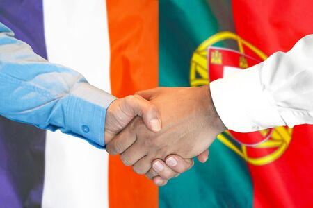 Business handshake on the background of two flags. Men handshake on the background of the France and Portugal flag. Support concept Foto de archivo