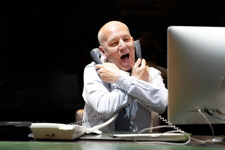 Elderly male hotel manager is under stress in front of a computer that answers the hotel's customer calls. A lot of phone calls. Funny facial expression, emotions, feelings, problems reaction, stress. Stock Photo