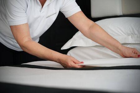 Elderly Maid making bed in hotel room. Housekeeper Making Bed