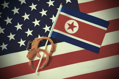 North Korea flag in handcuffs on the background of the American flag. US sanctions against North Korea.