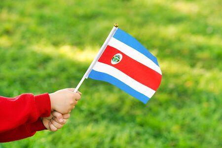 Hands of kid girl holding Costa Rica flag. Independence Day concept. Green grass background.