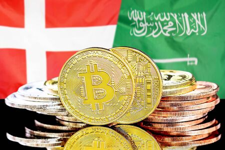 Concept for investors in cryptocurrency and Blockchain technology in the Denmark and Saudi Arabia. Bitcoins on the background of the flag Denmark and Saudi Arabia.
