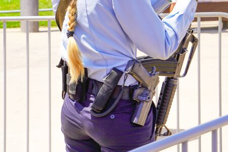 Police woman with a gun provides order on the street. Back view. Rear view of a woman in Israel.