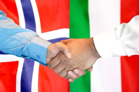 Business handshake on the background of two flags. Men handshake on the background of the Norway and Italy flag. Support concept