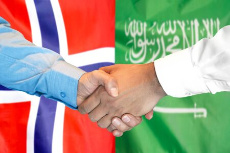 Business handshake on the background of two flags. Men handshake on the background of the Norway and Saudi Arabia flag. Support concept Banco de Imagens