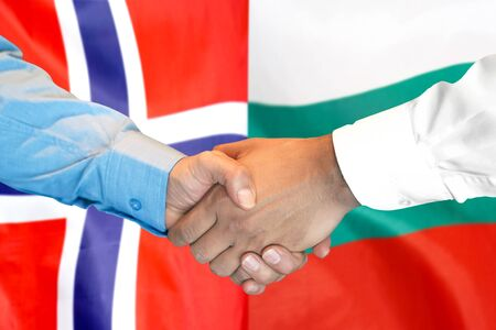 Business handshake on the background of two flags. Men handshake on the background of the Norway and Bulgaria flag. Support concept Banco de Imagens