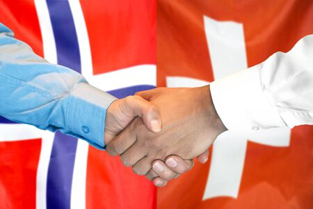 Business handshake on the background of two flags. Men handshake on the background of the Norway and Switzerland flag. Support concept