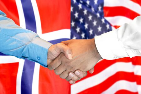 Business handshake on the background of two flags. Men handshake on the background of the Norway and United States of America flag. Support concept Banco de Imagens