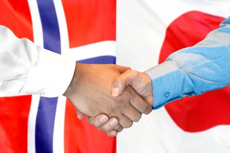 Business handshake on the background of two flags. Men handshake on the background of the Norway and Japan flag. Support concept