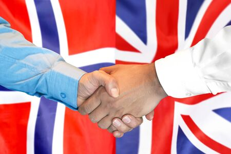 Business handshake on the background of two flags. Men handshake on the background of the Norway and United Kingdom flag. Support concept