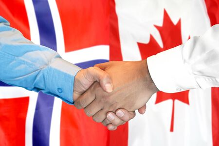 Business handshake on the background of two flags. Men handshake on the background of the Norway and Canada flag. Support concept