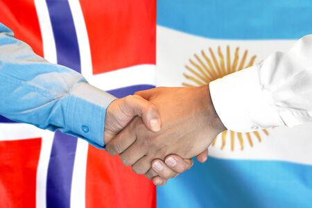 Business handshake on the background of two flags. Men handshake on the background of the Norway and Argentina flag. Support concept Banco de Imagens