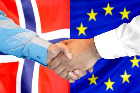 Business handshake on the background of two flags. Men handshake on the background of the Norway and European Union flag. Support concept