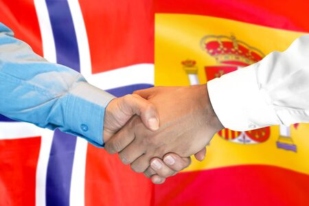 Business handshake on the background of two flags. Men handshake on the background of the Norway and Spain flag. Support concept Banco de Imagens