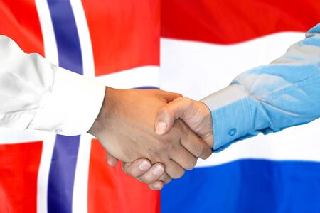 Business handshake on the background of two flags. Men handshake on the background of the Norway and Dutch flag. Support concept