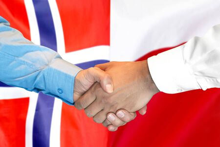 Business handshake on the background of two flags. Men handshake on the background of the Norway and Poland flag. Support concept Banco de Imagens
